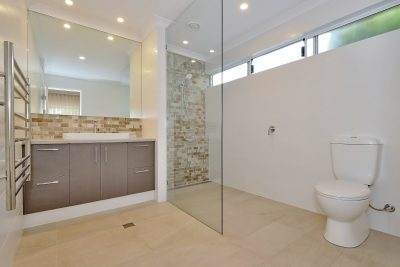 Bathroom renovation with frameless shower screen and feature tile by Mindful Homes