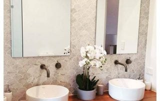 A bathroom with two mirrors and wash basins with a beautiful flowers in the middle