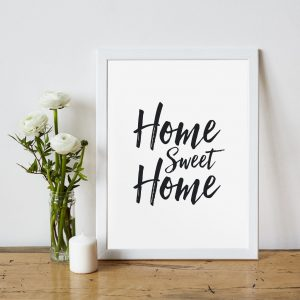 an image with home sweet home written In a frame and a candle and flower vase besides it
