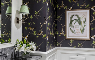 a beautiful image of bathroom with black floral walls, green lamp , a wall frame and flower vase