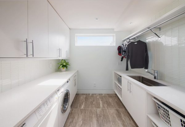 Modern laundry with hanging rails in Ottawa by Design First Interiors